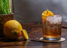 Alcoholic Old Fashioned Cocktail With Orange Slice And Lemon Peel Garnish