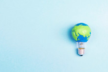 Light Bulb With Plasticine Earth Planet Model On Blue Background With Space For Text.