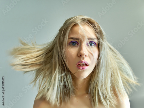 Closeup portrait concept of a beautiful blonde girl on a gray background. Hair develops in different directions.