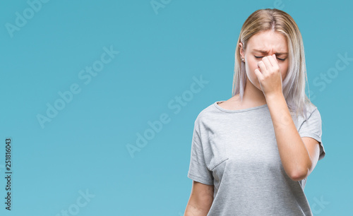 Fototapeta  Young blonde woman over isolated background tired rubbing nose and eyes feeling fatigue and headache