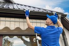 Man Installing House Roof Rain Gutter System