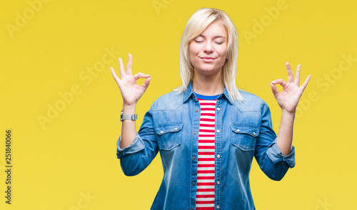 Fotobehang Zen Young beautiful blonde woman wearing denim jacket over isolated background relax and smiling with eyes closed doing meditation gesture with fingers. Yoga concept.