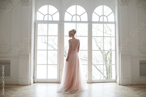 Tableau sur Toile The bride in a chic lush pink dress stands near the window in the beautiful hall
