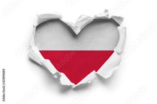 Heart shaped hole torn through paper, showing satin texture of flag of Poland Fototapet