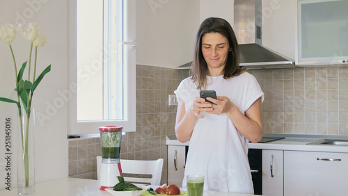 Photo  Young woman in white t-shirt prepares green smoothie in blender at home in the k