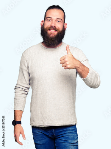 Fotomural Young blond man wearing casual sweater doing happy thumbs up gesture with hand