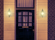 Wooden Front Door With Lighted Wall Lanterns Shining Light In The Dark, Dutch Architecture By Night