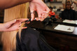 Close up of hairdressers hand cutting blonde hair. Doing new haircut in beauty salon
