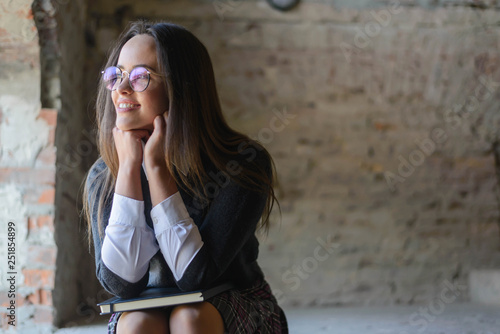 Fotografía  Pretty girl in uniform leaning on elbows and looking to the window on the loft b