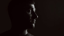 Portrait Of A Guy On A Black Background In Low Key