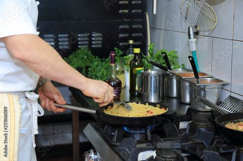 Fototapeta Kucharz w restauracji podgrzewa spaghetti na patelni w kuchni. obraz