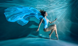 Girl portrait posing underwater in blue fashion dress in swimming pool alone in the deep