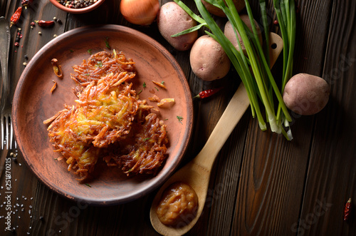 Top view at flat lay fresh homemade tasty potato pancakes in clay dish with appl Canvas Print