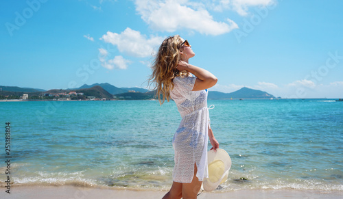 Fotografija  Young woman in white clothing refreshing at the ocean beach, China