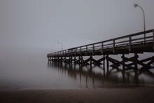 Fishing Pier Disappearing Into The Sea In Foggy Conditions. Dramatic Seascape, Creepy Moody Scene.