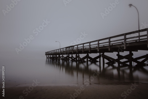 Valokuvatapetti Fishing pier disappearing into the sea in foggy conditions
