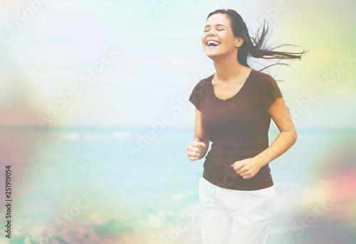 Obraz na plátne  Young woman on field under sunset light