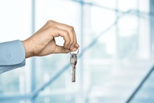 House Key In Hand On Blurred B...