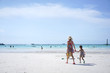 Young Asian mother holding her child hand walking on the beach to play the white sand. Seen from their back. Happy vacation on the sea concept.