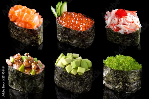 Fototapeta Set sushi gunkan from salmon, caviar, tuna, shrimp, avocado and smoked eel on black background. Traditional Japanese cuisine obraz