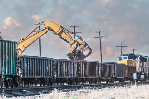 Fotografie, Obraz  Excavator loading old railroad ties in open boxcars.
