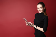 Portrait Of A Beautiful Smiling Caucasian Woman In A Black Dress Using A Tablet On A Red Background