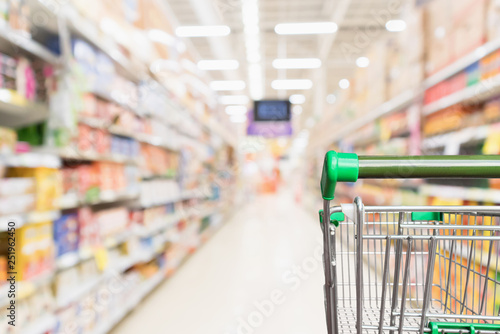 Empty green supermarket shopping cart with abstract blur grocery store aisle def Wallpaper Mural