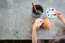 Asian Girl Studying And Learning The Art,the Kid Using Paintbrush To Painting Water Color On The Potted Plant Made Of Pottery,concept Art Learning And Education,hobby And Activity