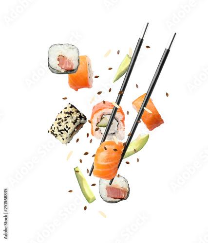 Fototapeta Tasty sushi rolls, avocado and chopsticks on white background obraz