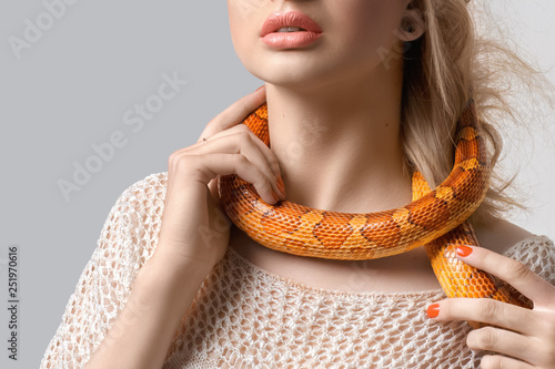 Fotomural Young, beautiful, woman with snake around her neck on grey background