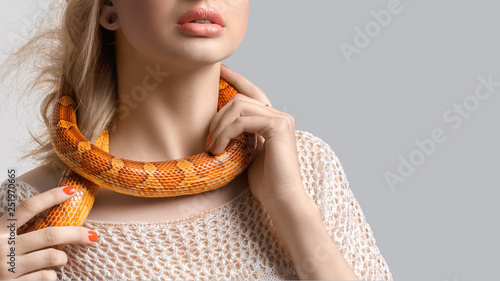 Fotografía Young, beautiful, woman with snake around her neck on grey background