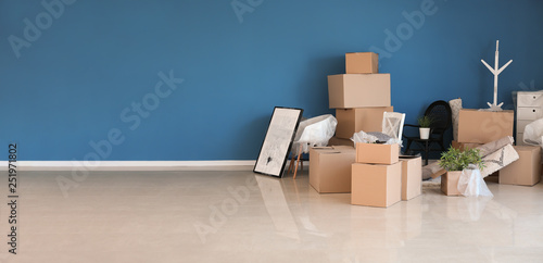 Obraz Carton boxes and interior items prepared for moving into new house near color wall - fototapety do salonu