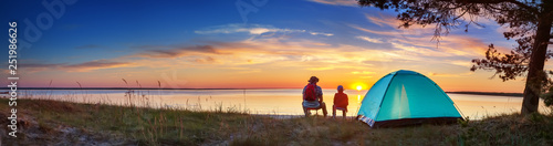 Foto Family resting with tent in nature at sunset