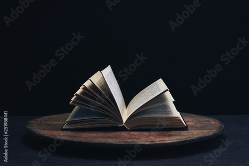 Fotografía  One open old book on a round wooden table