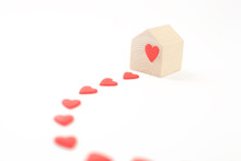 Miniature Wooden House With Road Of Red Hearts Leading To The House On White Background. House Full Of Love Concept.