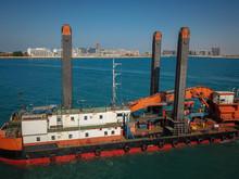 Ship Digging Sand In Background Of Dubai, UAE