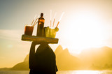 Scenic sunset view of Two Brothers Mountain with an unrecognizable silhouette of a beach vendor carrying caipirinha cocktails passing in silhouette at Arpoador in Rio de Janeiro, Brazil