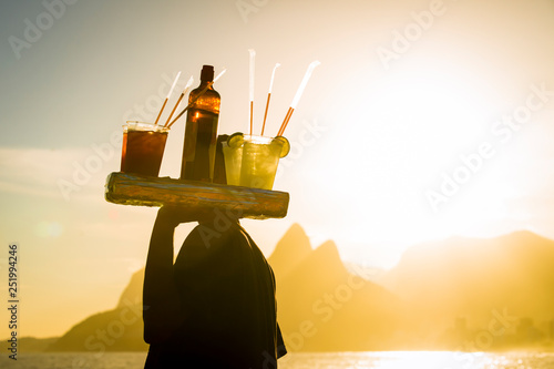 Foto auf AluDibond Rio de Janeiro Scenic sunset view of Two Brothers Mountain with an unrecognizable silhouette of a beach vendor carrying caipirinha cocktails passing in silhouette at Arpoador in Rio de Janeiro, Brazil
