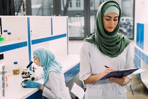 Fotografia  concentrated female muslim scientists using microscope and writing in clipboard