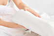 Female hands hold and show an orthopedic pillow on a white bed. Comfortable sleep and healthy spine