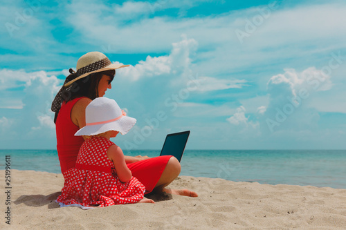 Photo sur Toile Kiev mother and little daughter looking at laptop on beach