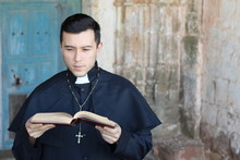 Ethnic Young Priest Reading Is...