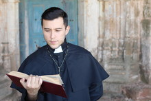 Ethnic Young Priest Reading Isolated