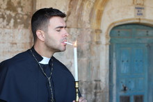 Priest Lighting A Cigarette With A Candle