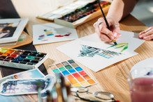 Artist Workplace. Watercolor Painting Creation. Hand Doing Color Brushstrokes With Sketches And Palette Supplies Around.