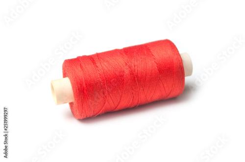 Photo closeup of orange sewing thread spool bobbin on white background