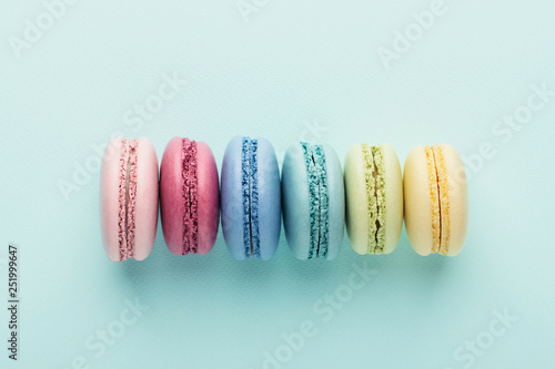Aluminium Prints Macarons Row of colorful macarons on turquoise background. Top view.