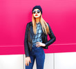 canvas print picture - Fashion portrait stylish blonde woman in rock black style jacket, hat posing on city street over colorful pink wall background