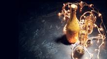 Image Of Golden Champagne Bottle, Two Wine Glasses, Burning Garlands