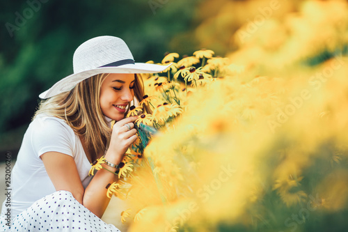 Foto auf Gartenposter Orange Beautiful young woman smelling yellow flower in the park.